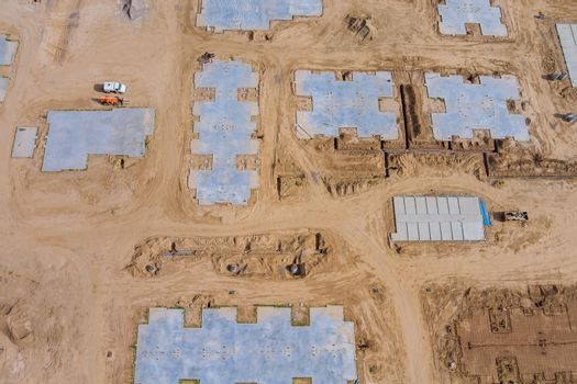 Construction of aerial top view on pouring the foundation for a new house with suburbs development.
