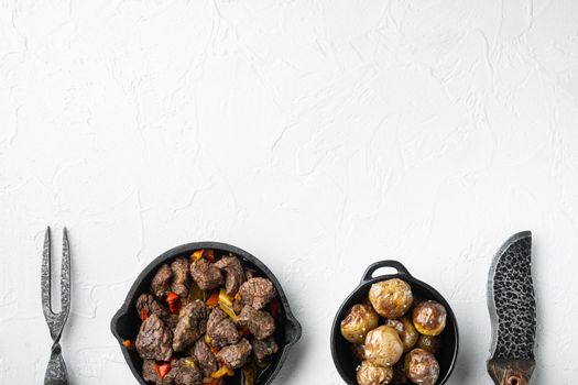 Mongolian beef, pieces of beef stewed in soy sauce, in cast iron frying pan, on white stone surface, top view flat lay, with copy space for text