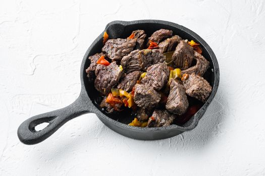 Beef meat stewed with potatoes, carrots and spices, in cast iron frying pan, on white stone surface