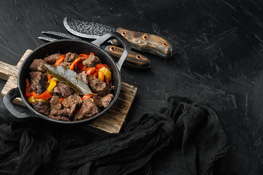 Beef meat and vegetables stew, in cast iron frying pan, on black stone background, with copy space for text