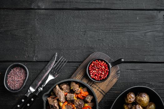 Bangin beef stew, in cast iron frying pan, on black wooden background, top view flat lay, with copy space for text