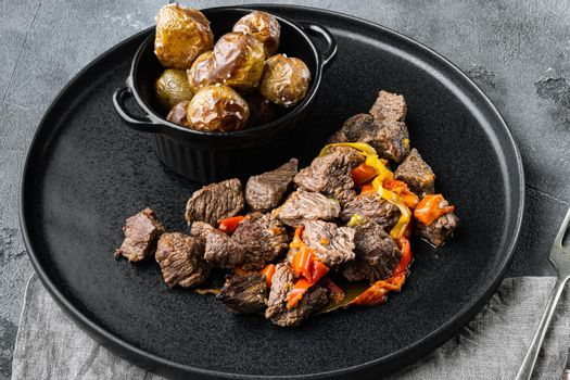 Beef bourguignon stew with vegetables, on gray stone background