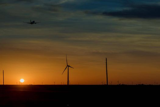 Wind turbine farms in the colorful sunset showing renewable energy works, wind energy blows into West Texas