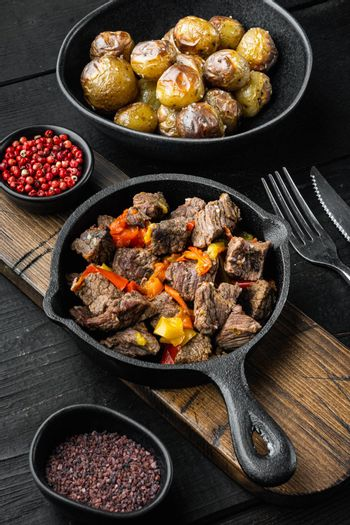 Beef meat stewed with potatoes, carrots and spices, in cast iron frying pan, on black wooden background