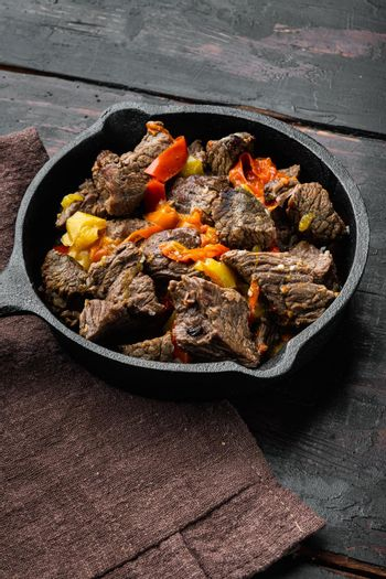 Bangin beef stew, in cast iron frying pan, on old dark wooden table