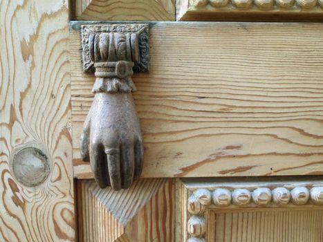 Old bronze knocker on a wooden door