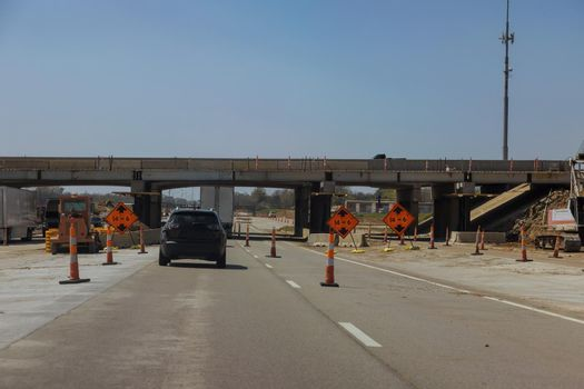 Construction for renewing damages on pillars of concrete bridge of a under renovation road modern road interchange in USA