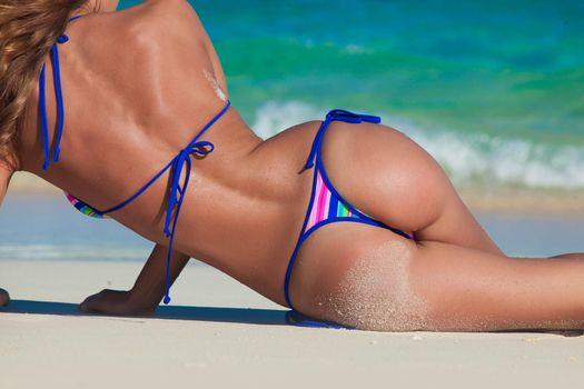 Tanned woman body in bikini laying in beach, blue sea water in background