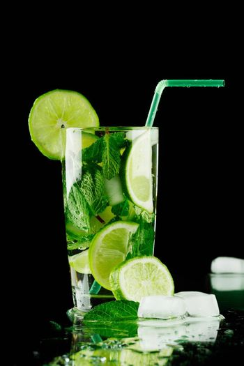 Mojito cocktail with lime, mint and ice on black background