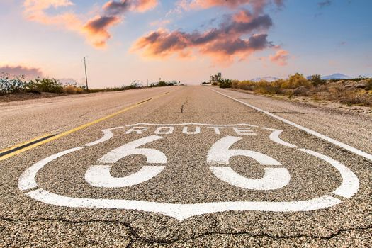 Route 66 road sign with blue sky background. Historic street with nobody. Classic concept for travel and adventure in a vintage way.