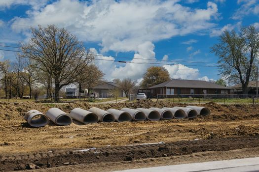 Stacks of concrete sewage pipes on the ground prepare for underground installation the view construction road place in the blue sky background