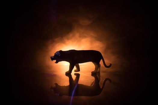 Silhouette of a tiger miniature standing at foggy night. Creative decoration with colorful backlight with fog. Selective focus