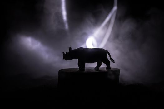 Silhouette of a Rhino miniature standing at foggy night. Creative table decoration with colorful backlight with fog. Selective focus