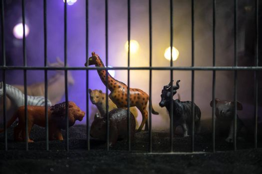 A group of animals inside a cage miniature. Wild animals in the zoo concept. Burning colorful background. Selective focus.