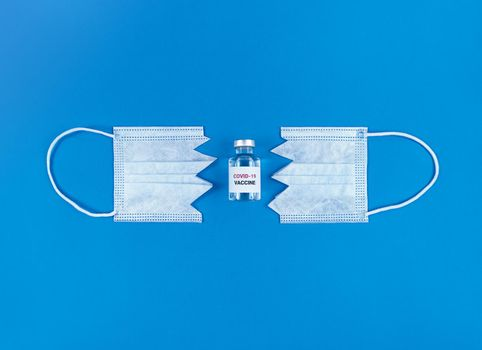 Vial with covid19 vaccine between two parts of cut medical mask on blue background.
