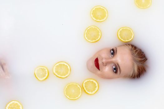 Young woman takes a bath with milk and citrus fruits.