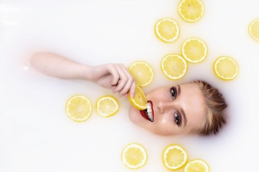 Young woman takes a bath with milk and citrus fruits. Woman eats a lemon.