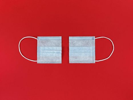 Medical disposable face mask cut in half on a red background.