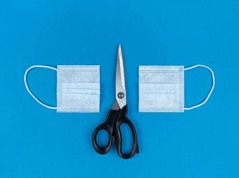 Medical disposable face mask cut in half and scissors on blue background.