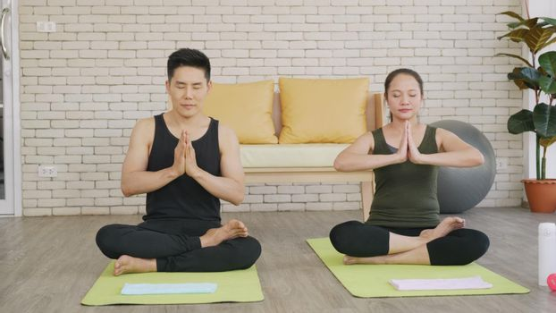 Happy Asian beautiful lifestyle family couple doing YOGA sitting meditating on lotus pose workout at home together on mat with eyes closed. Two people sport healthy concept.