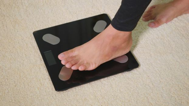 Asian young woman leg stepping standing on floor electric scales, female working out at home in living room, female stand on digital weighing machine. Healthy weight loss control concept, slow motion