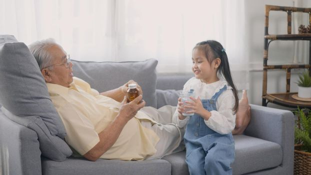 Asian granddaughter brought medicine and water for Grandpa to eat on the sofa in the lounge, Senior old man taking pills medicine time, granddaughter take care older with love