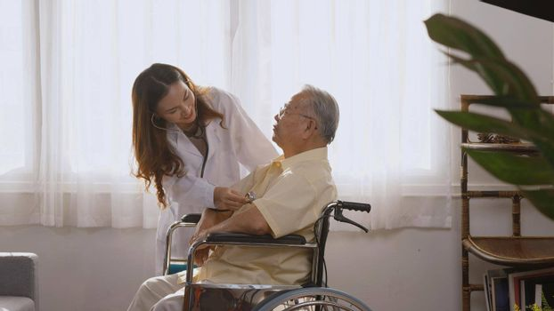 Female nurse doctor wear white uniform cardiologist examining patient senior or elderly old man during sit on wheelchair listening checking heartbeat using stethoscope at home, Health visitor concept