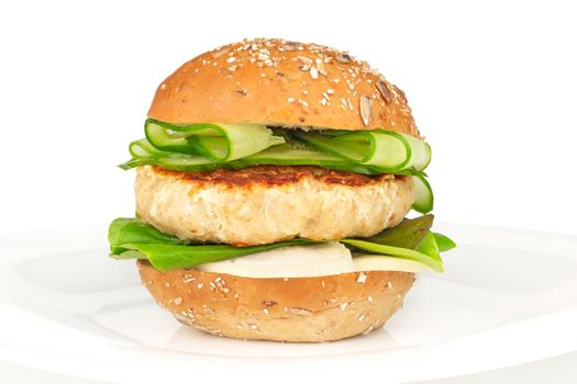 Fishburger fish burger with cod cutlet cucumber lettuce goat cheese dzatziki tartarus sauce and grain cereal bread on plate isolated on white background
