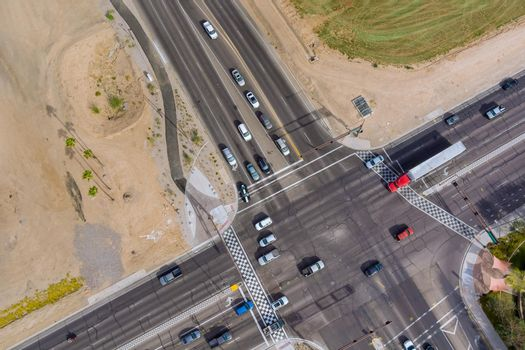 Major asphalt road intersection with multiple highways lanes, with a traffic light a pedestrian crossing, seen from aerial panorama view