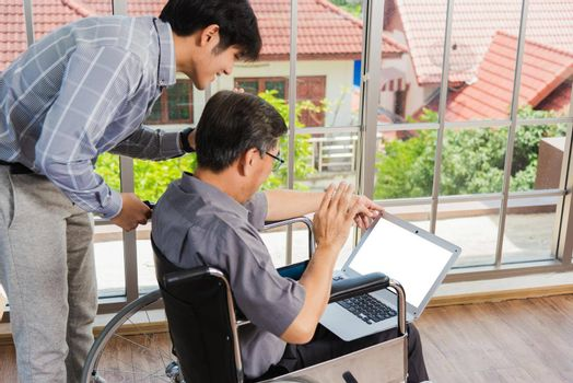 Asian senior disabled businessman in a wheelchair with laptop computer discuss together with team in office. Old father man sitting wheelchair and his son talking video calls conference on laptop