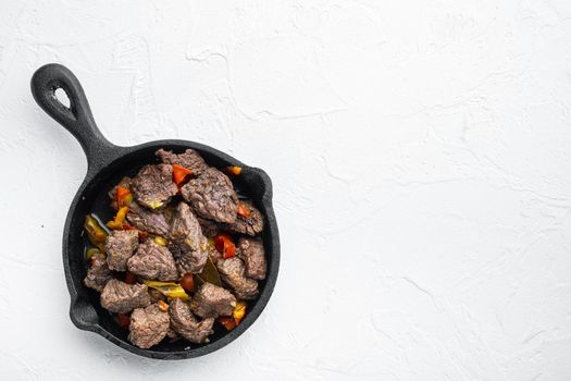 Beef bourguignon stew with vegetables, in cast iron frying pan, on white stone surface, top view flat lay, with copy space for text