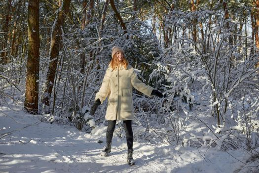 Happy woman walking in snow outdoors nature. Joyful young person relaxing on an outdoor walk activity in snowy forest landscape