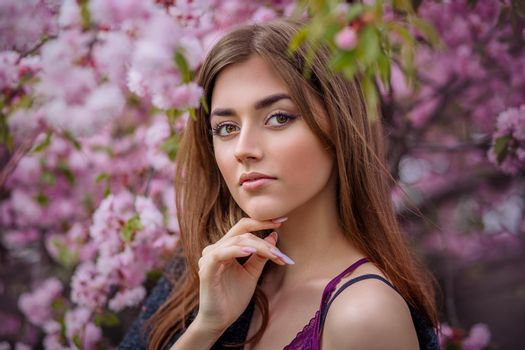 beautiful young woman in blooming cherry blossoms garden in early spring