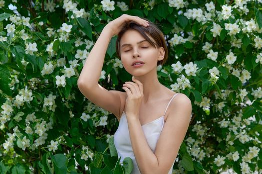 Attractive modest young woman natural makeup in a white dress outdoors against the background of blooming jasmine