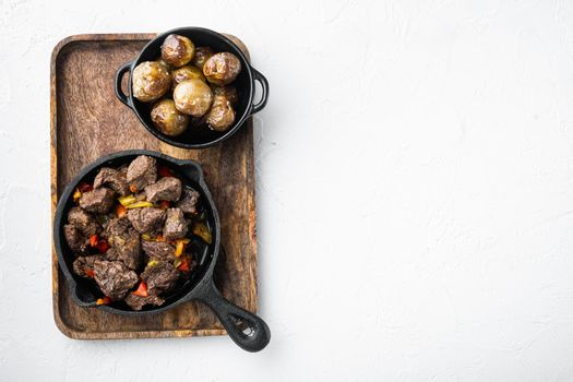 Irish stew made with beef, potatoes, carrots and herbs, in cast iron frying pan, on white stone surface, top view flat lay, with copy space for text