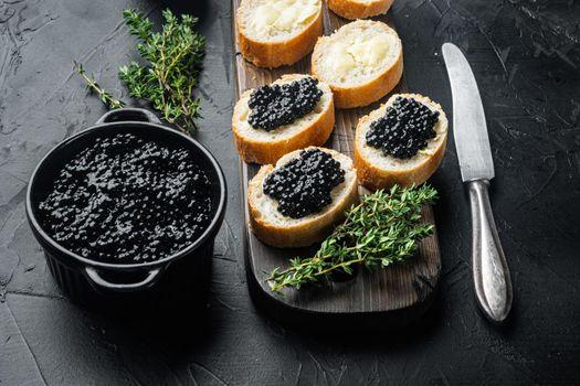 Black caviar served on baguette, on black background