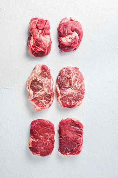 Raw set of alternative beef cuts Chuck eye roll, top blade, rump steak. Organic meat. White textured background. Top view.