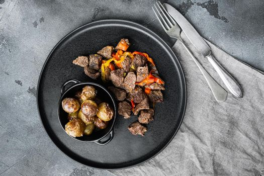 Beef meat stewed with potatoes, carrots and spices, on gray stone background, top view flat lay