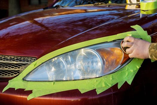 Headlight restore in the worker polishes optics of headlights of the car with the hand tool at car service station