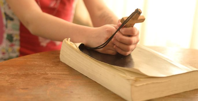 teenager girl praying to God holding a wooden cross,focus on cross.Concept of faith,hope and love