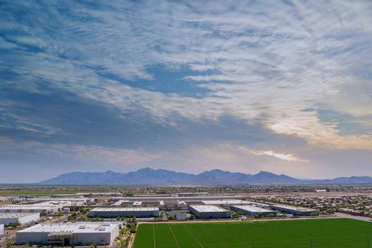 Aerial panoramic view goods warehouse logistics center industrial city zone near neighbourhood suburban homes in Avondale residential area landscape with among desert the Arizona USA.