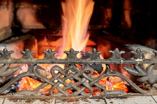 Cast-iron fireplace grille against the background of burning coals