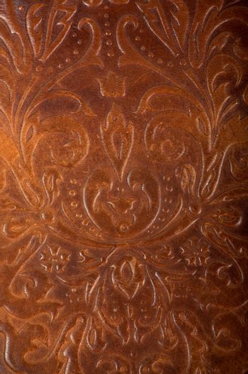 brown leather book or journal cover with a decorative floral ornament