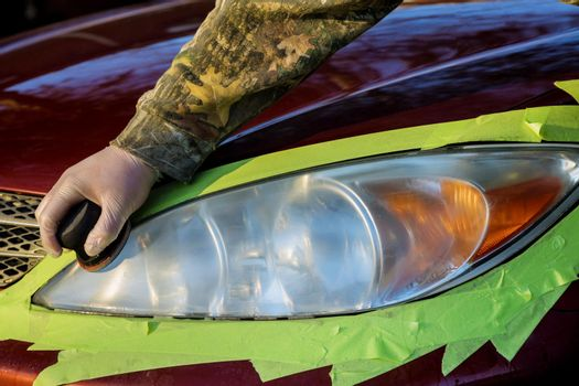 The worker polishes optics of headlights of the car with the hand tool on headlight restore