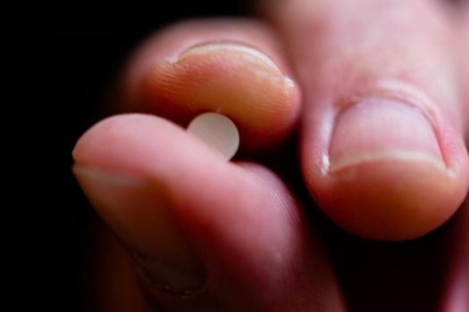 Fingers hold tablet, macro shot