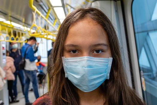 Young tween girl wearing surgical mask on subway