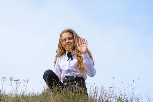 A girl in a white shirt with a bow tie sits on the ground in a field against the background of the sky and waves a pen to the frame