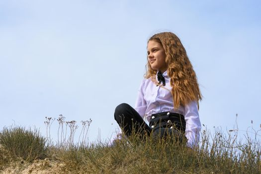 A girl in a white shirt with a bow tie sits on the ground in a field against the background of the sky