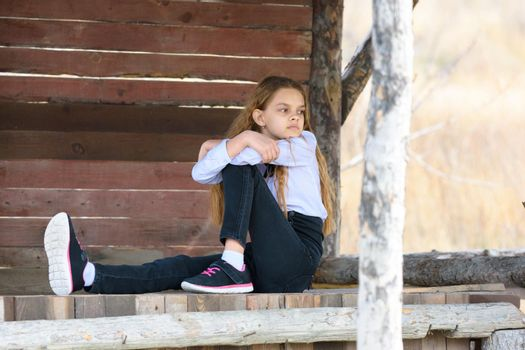 A girl sits on a wooden table against the background of a wall of boards and looks into the distance