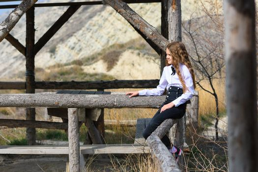 A girl sits on a wooden fence near an old gazebo made of wooden beams on a sunny warm day